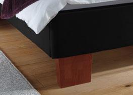 Das Polsterbett Lopo aus Kunstleder und Füßen aus Massivholz