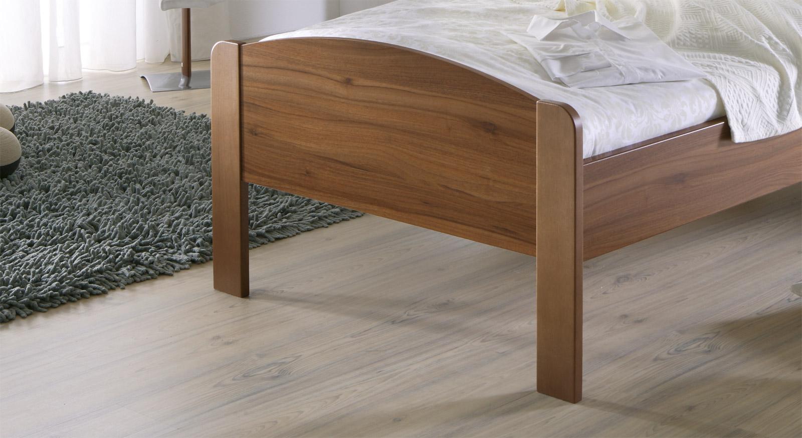 Schlichtes Bett San Martino mit stabilem und elegantem Fußteil - hier in Nussbaum Dekor.